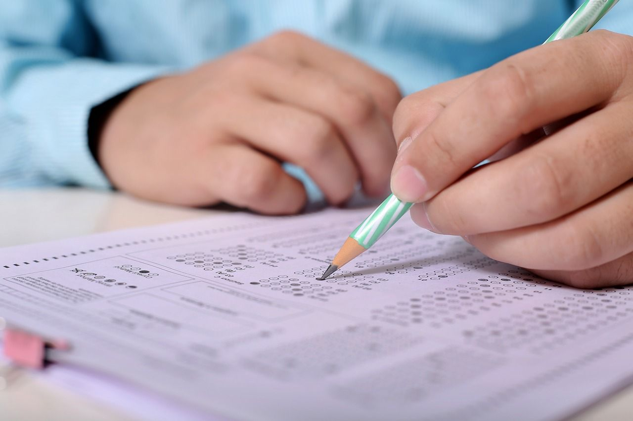 Man with pencil and scantron writing exam