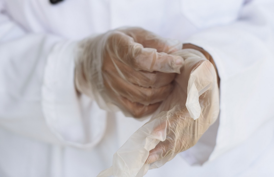 Doctor changing gloves before test post-mortem exam