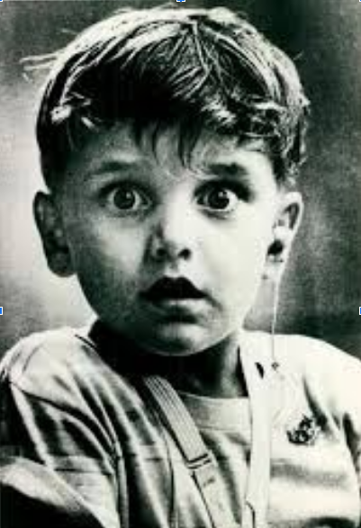 Boy with hearing aid looking surprised