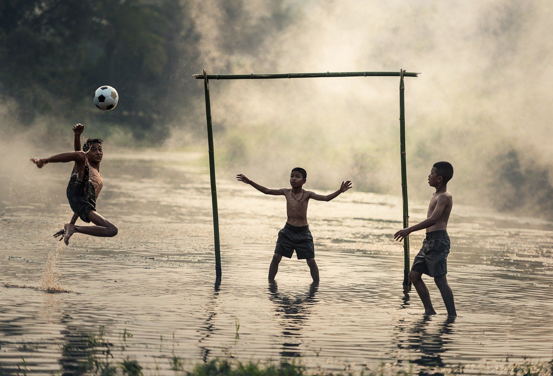 Children playing soccer in water