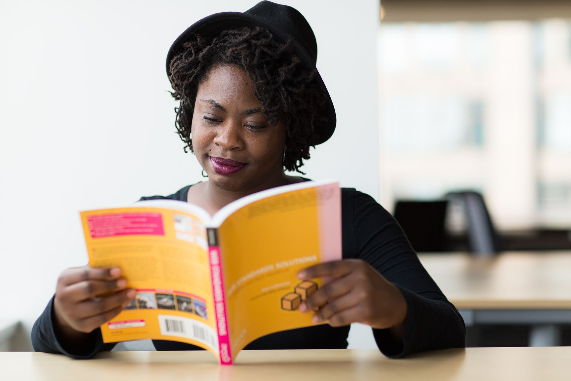 Lady with hat reading book studying for test