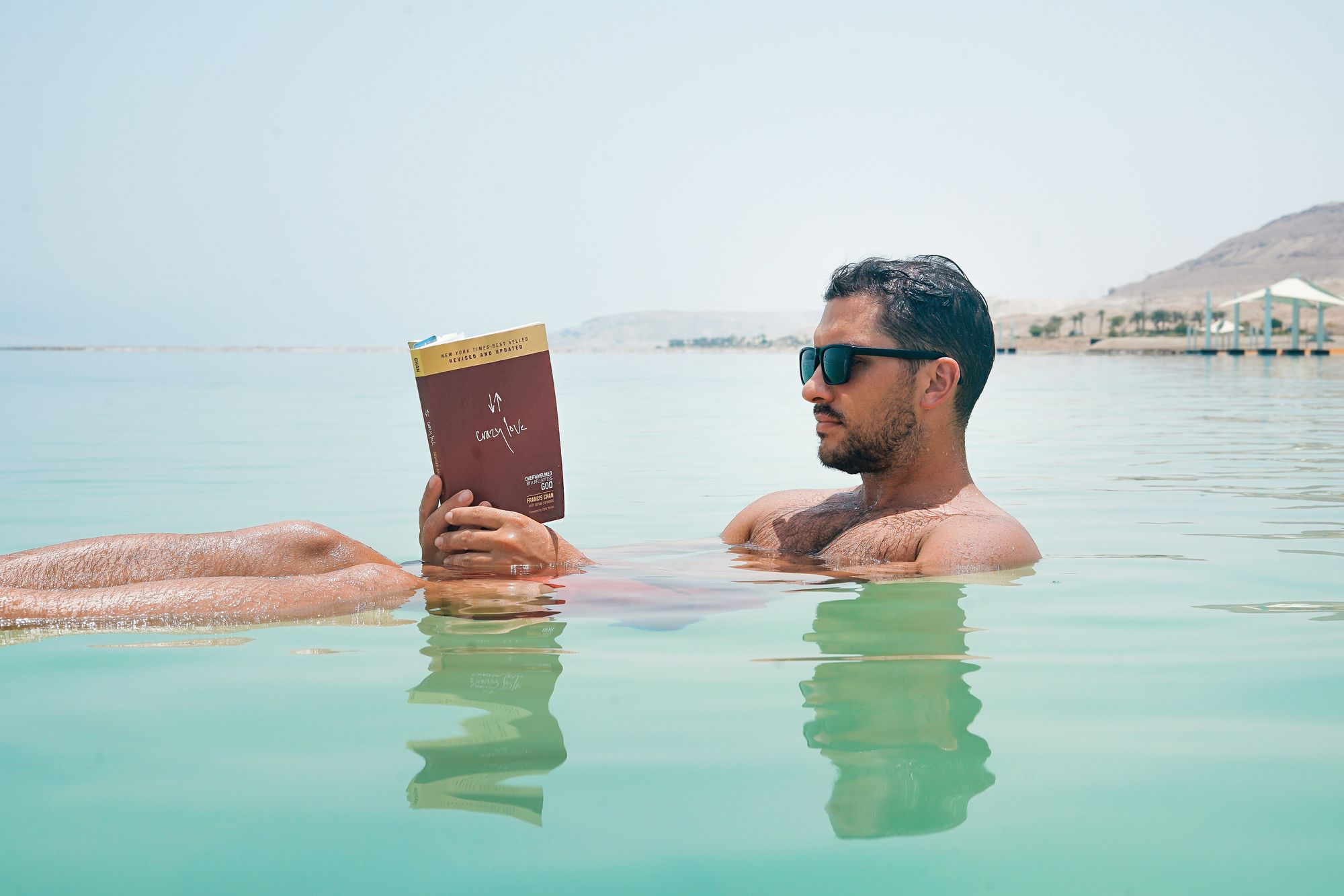 Man floating in the water with a book