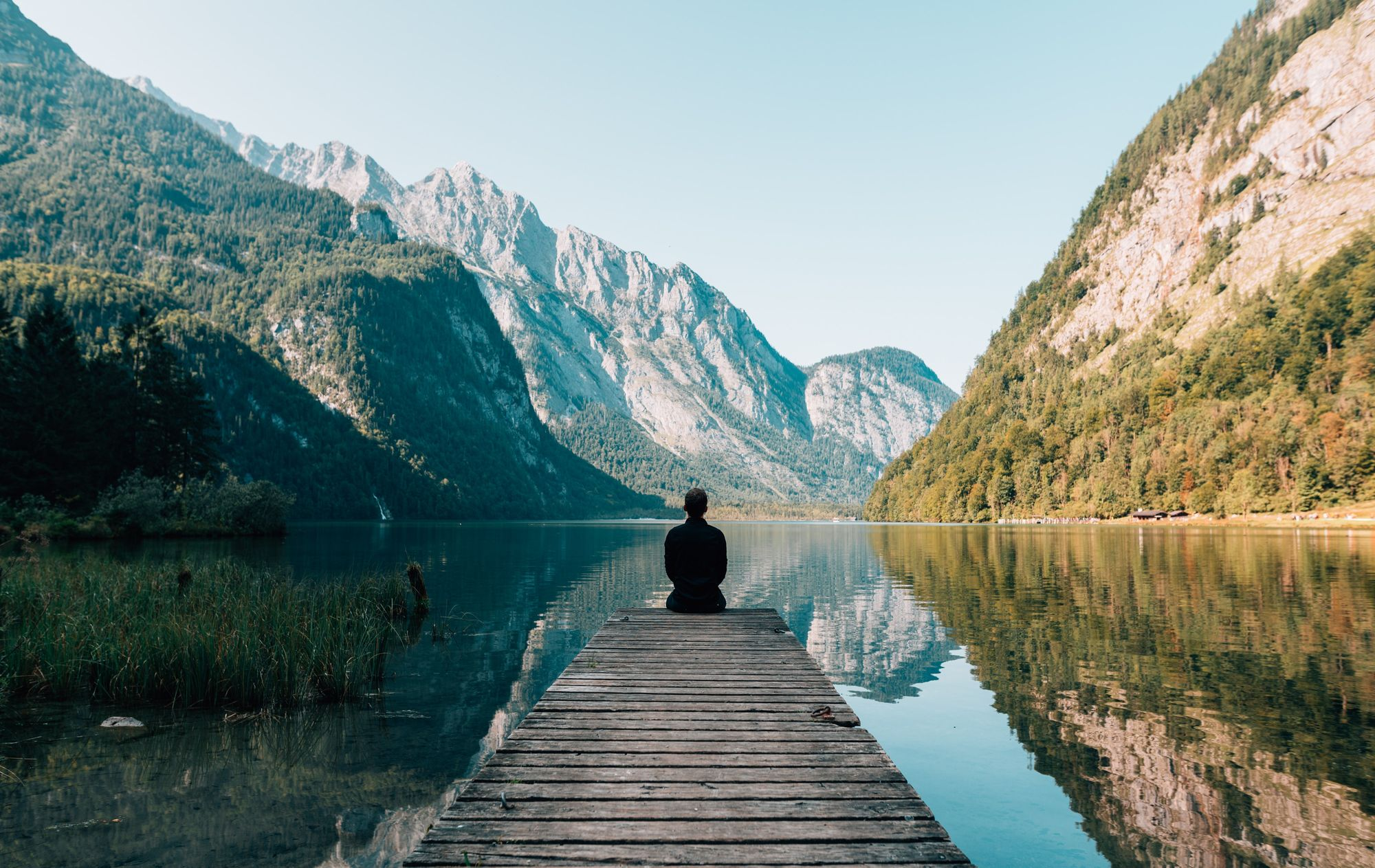 Man sitting in front of mountains and lakes