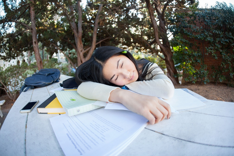 Girl sleeping on table tired from studying