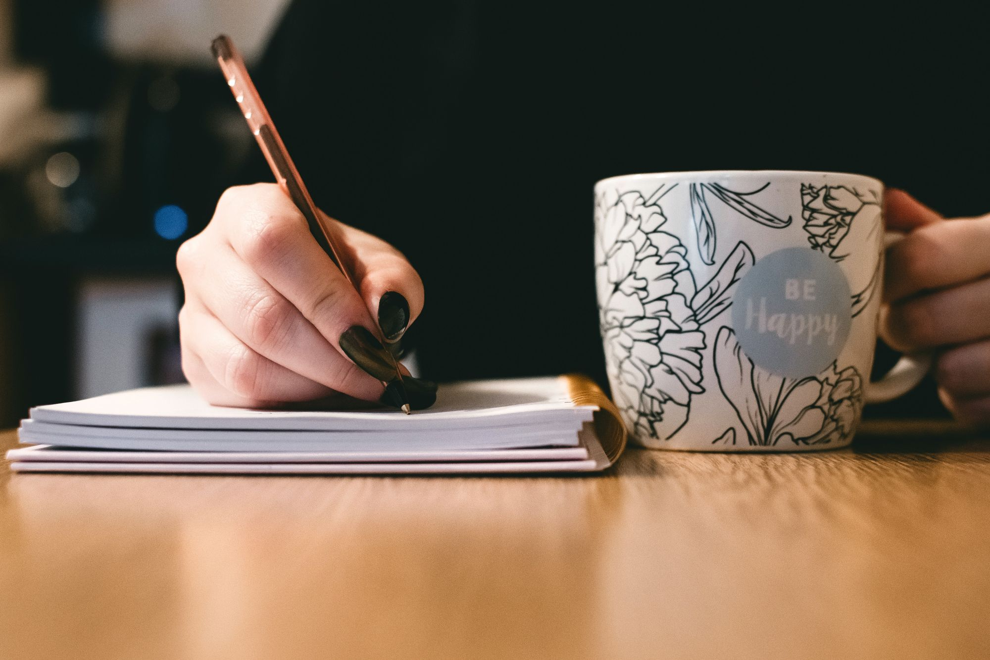 Woman writing in notebook with mug learning a new language