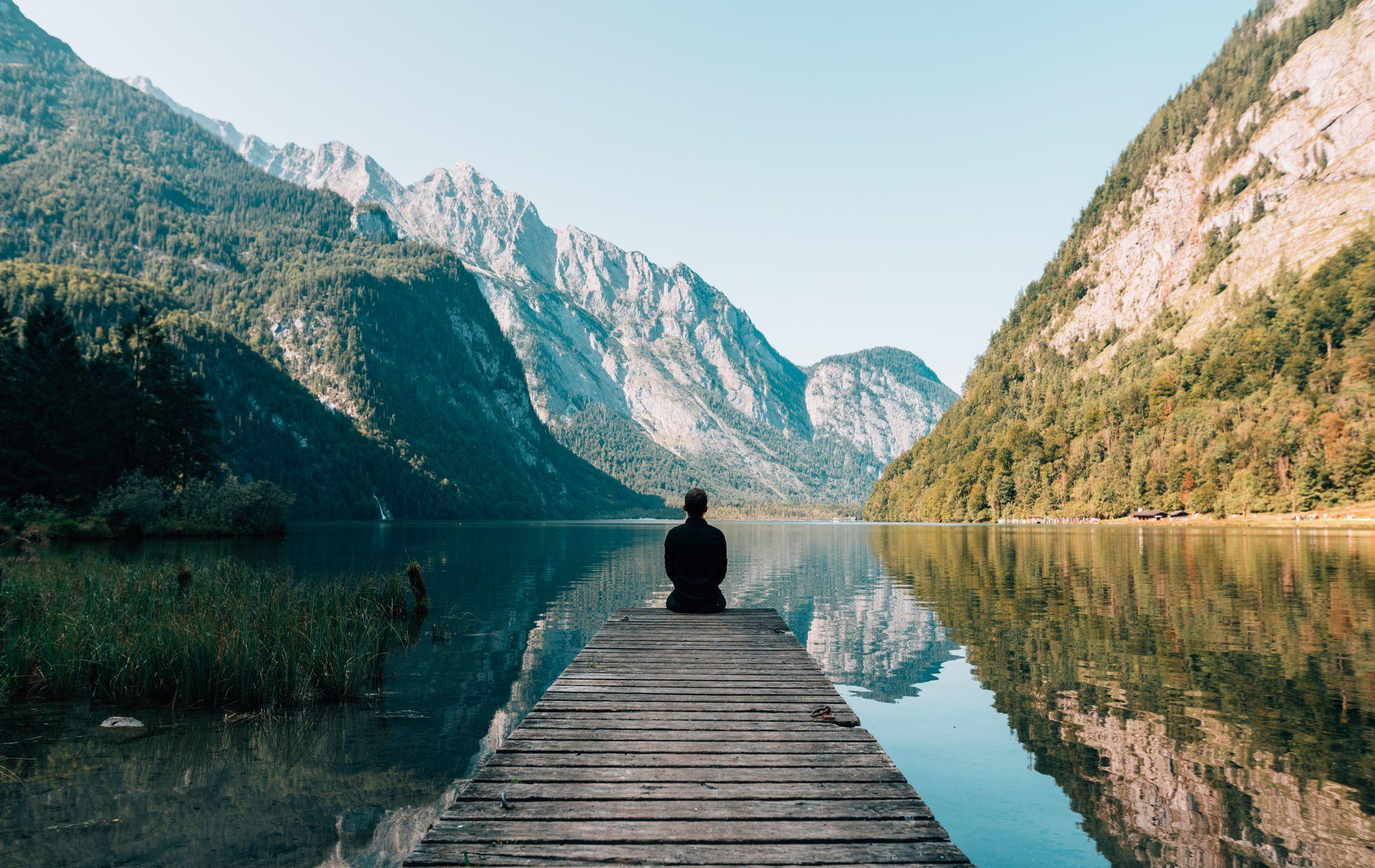 Man on wharf at serene lake eliminating stress