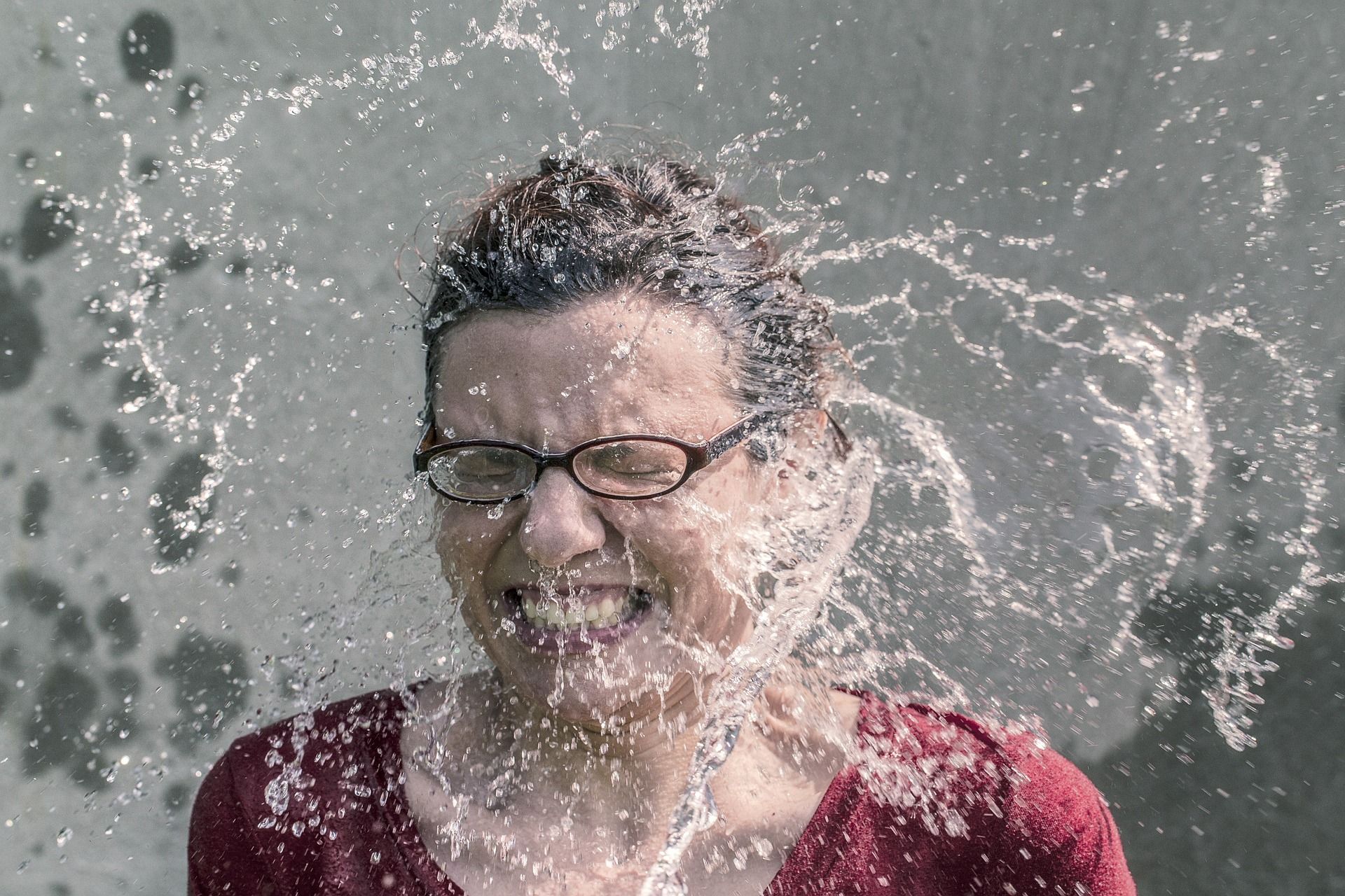 Lady getting splashed with water in the face