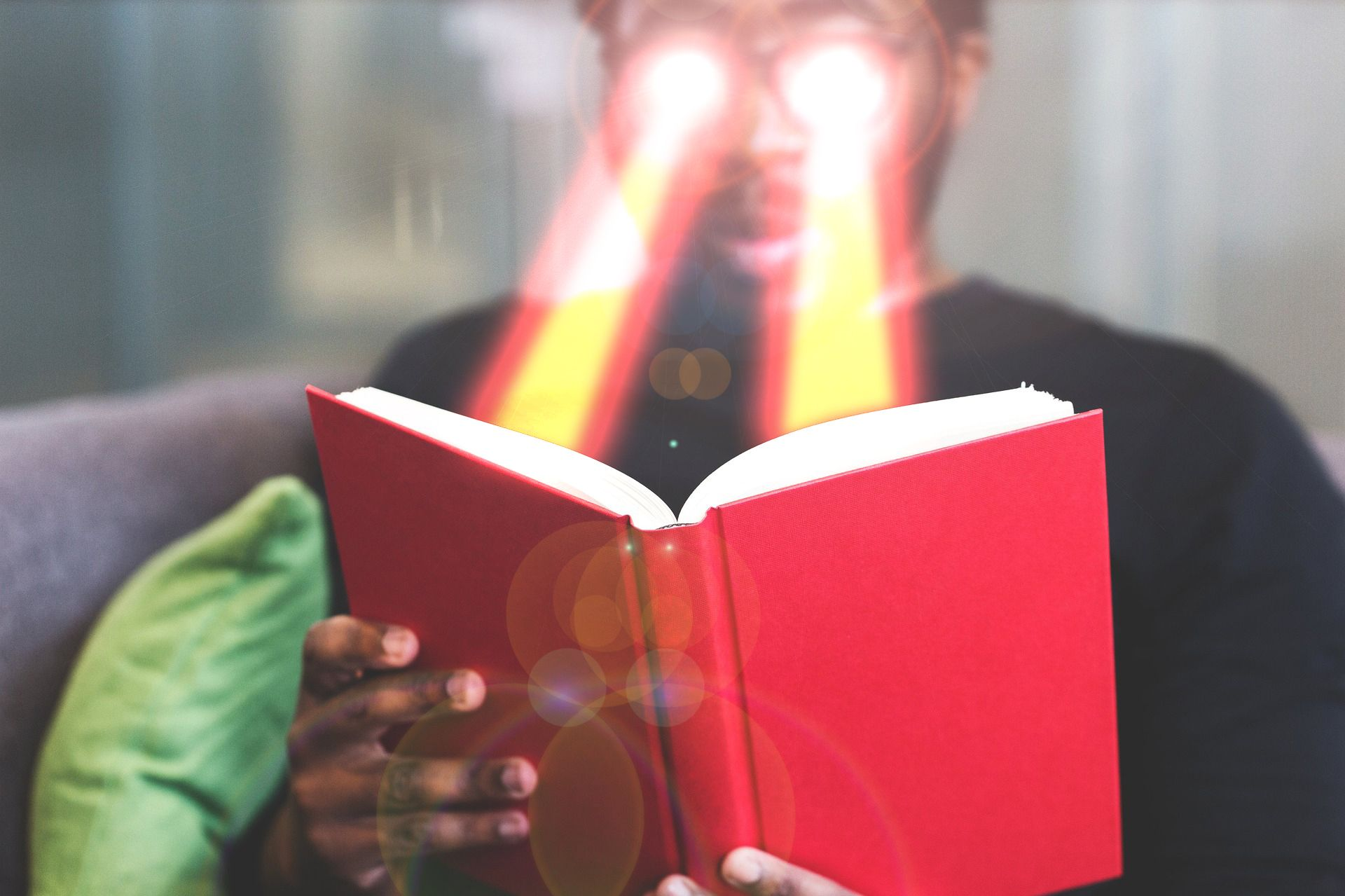 Man reading a book with lasers coming out of his eyes