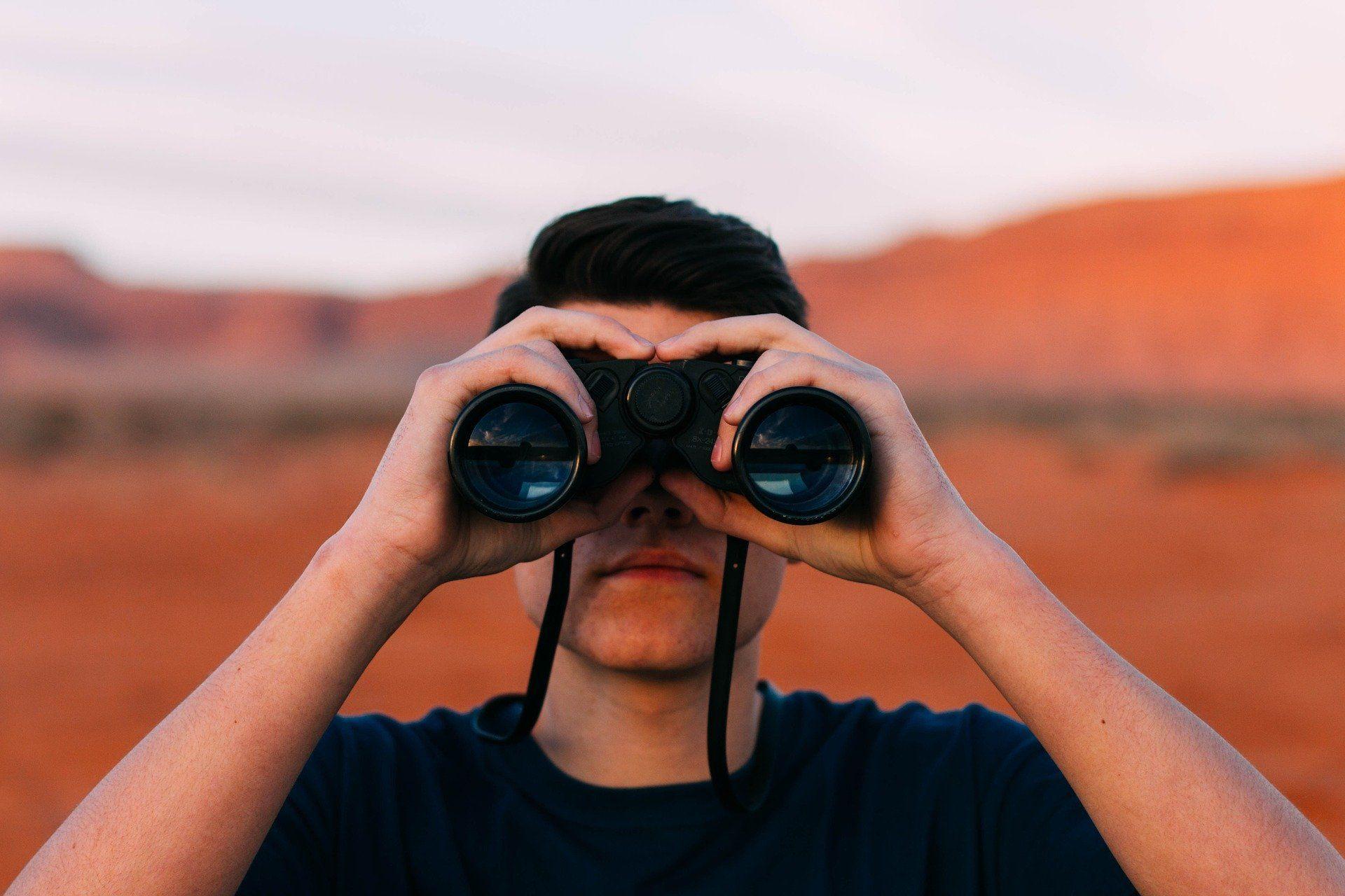 Man looking through binoculors