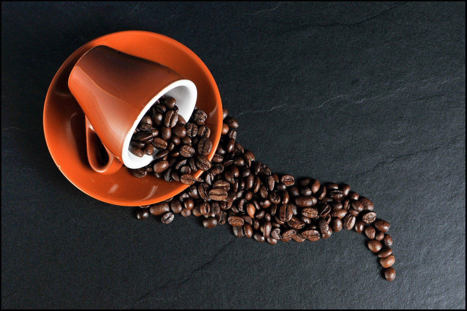A spilled cup filled with coffee beans