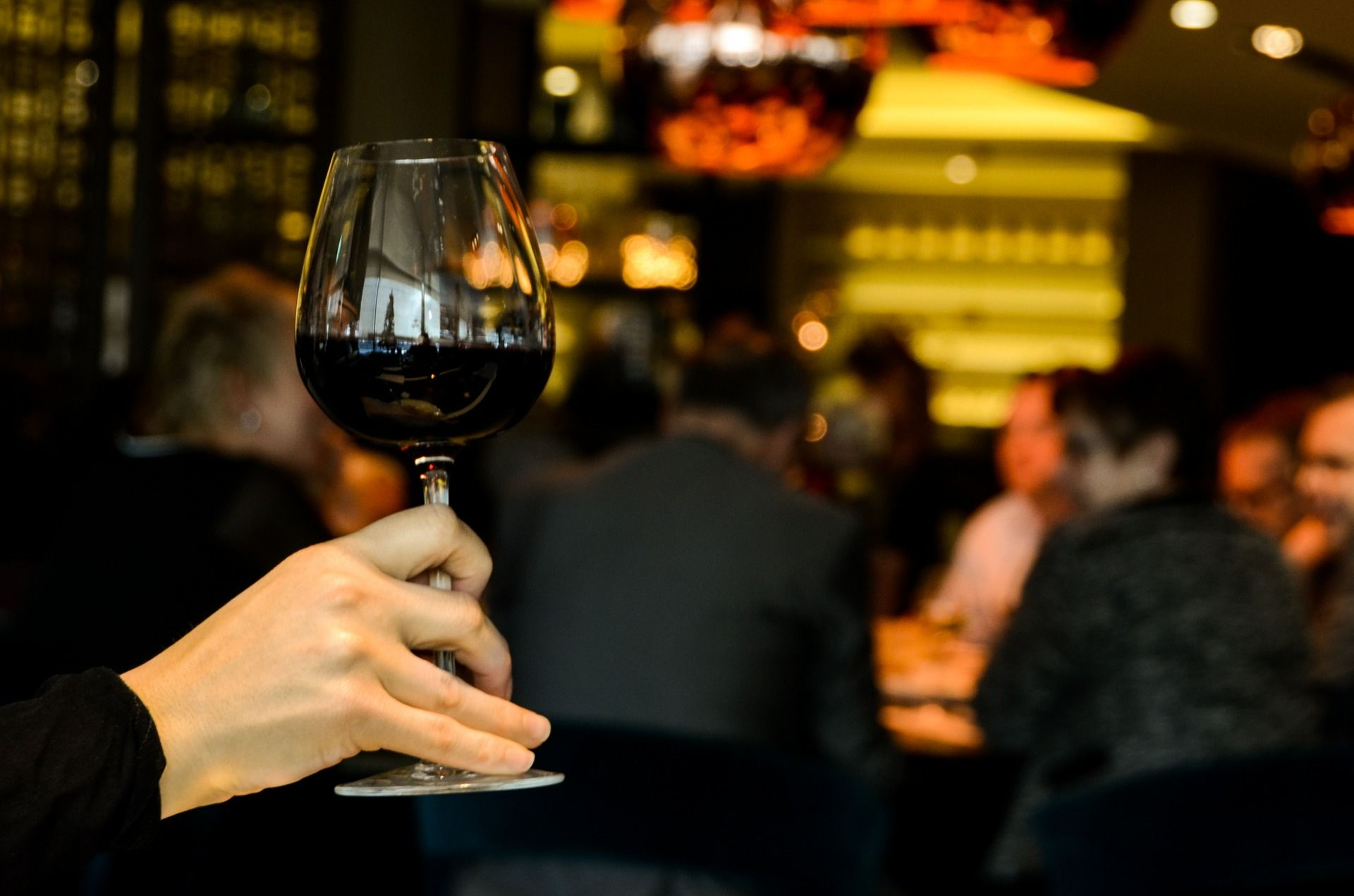 Hand holding a wine glass with red wine; WSET Level 2 exam