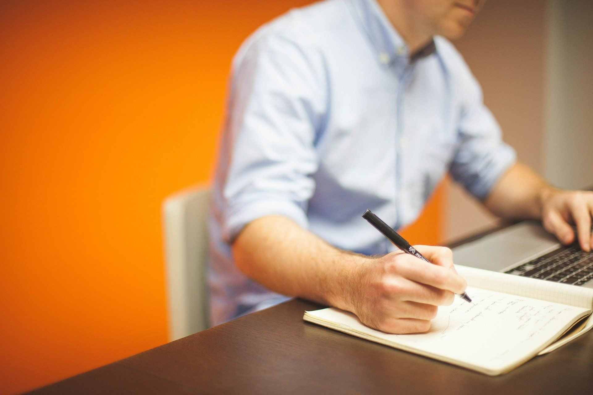 Man writing on paper on a desk; employee development