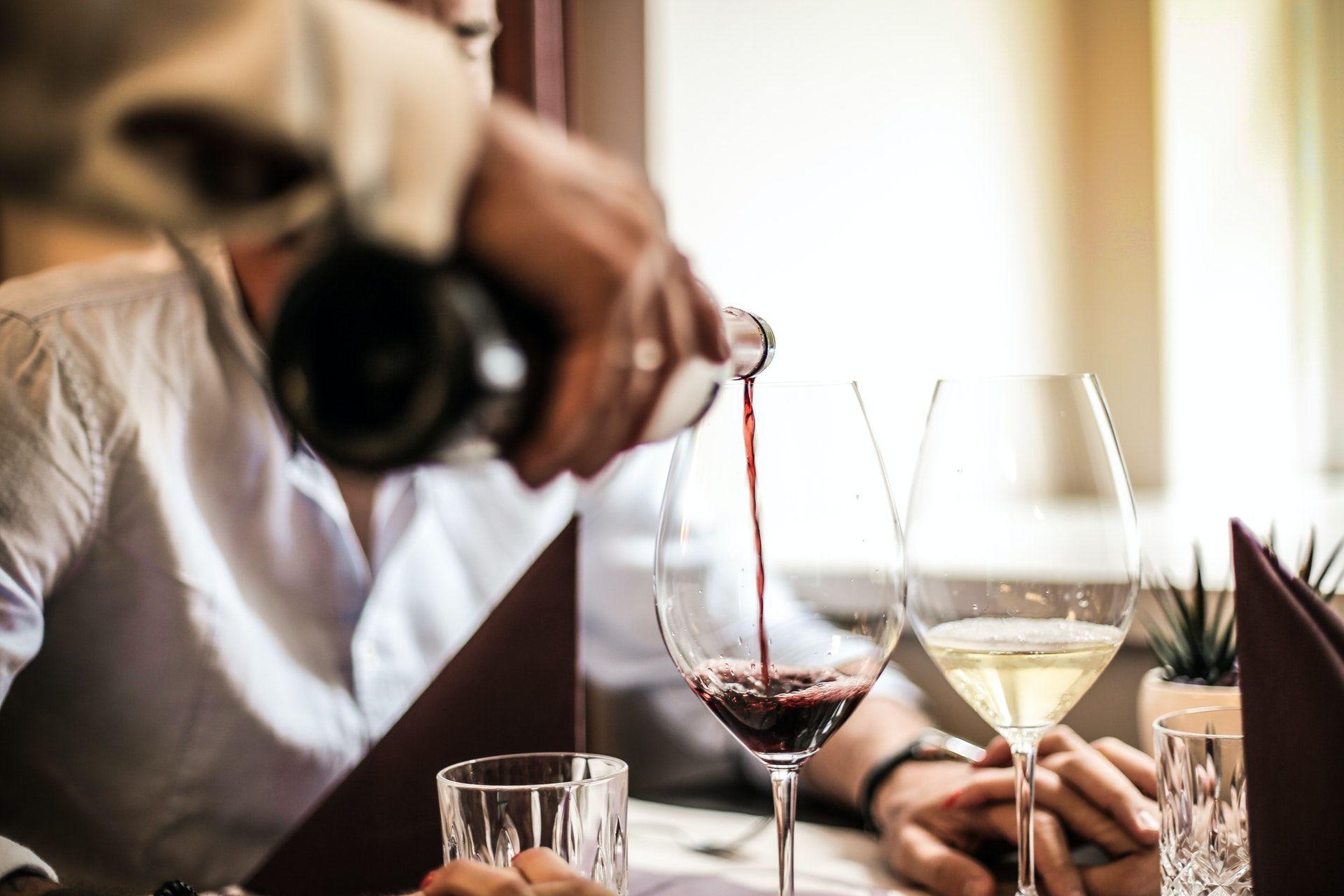 Sommelier pouring wine; WSET Level 3 exam