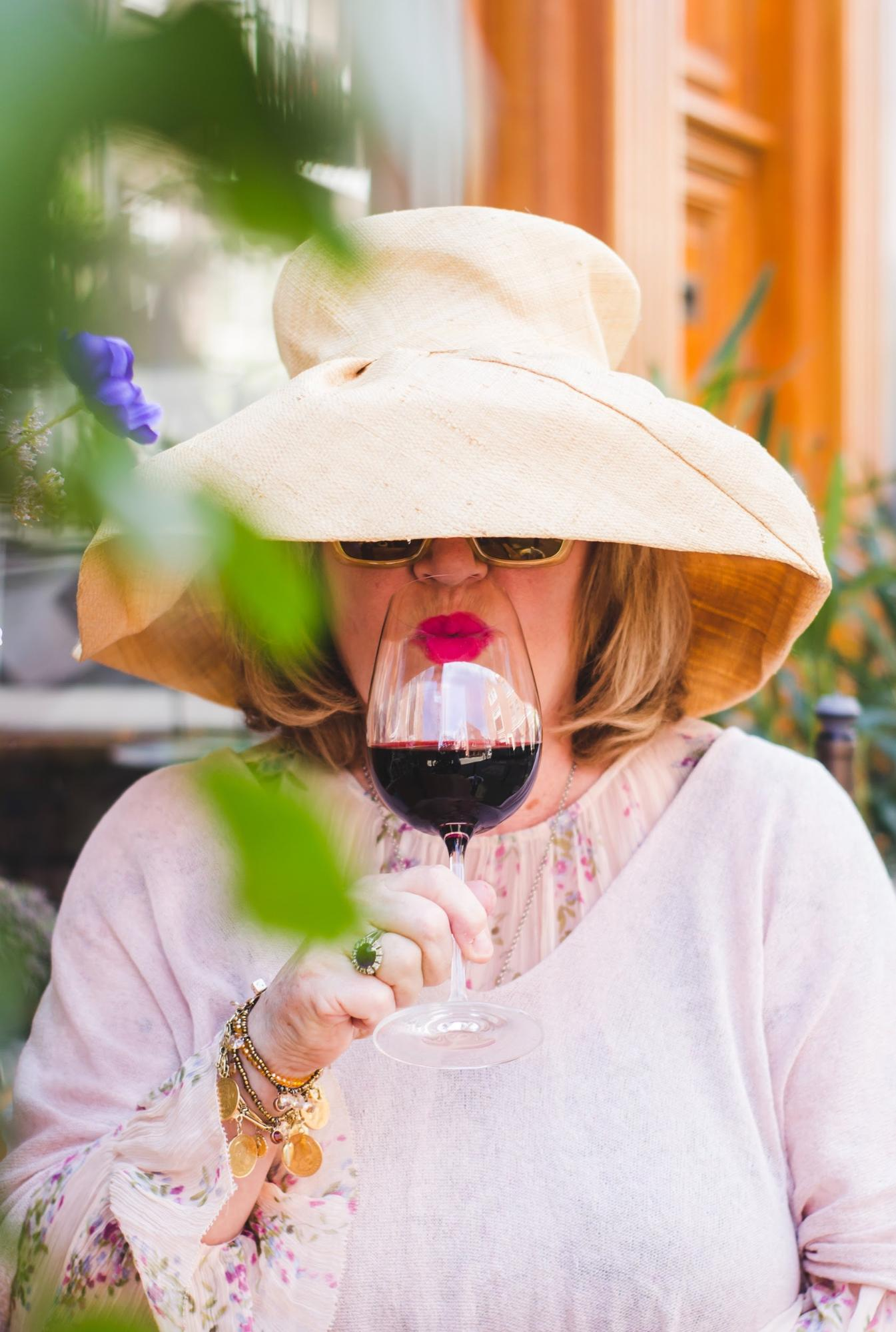 Lady in hat drinking red wine; WSET Level 3 exam