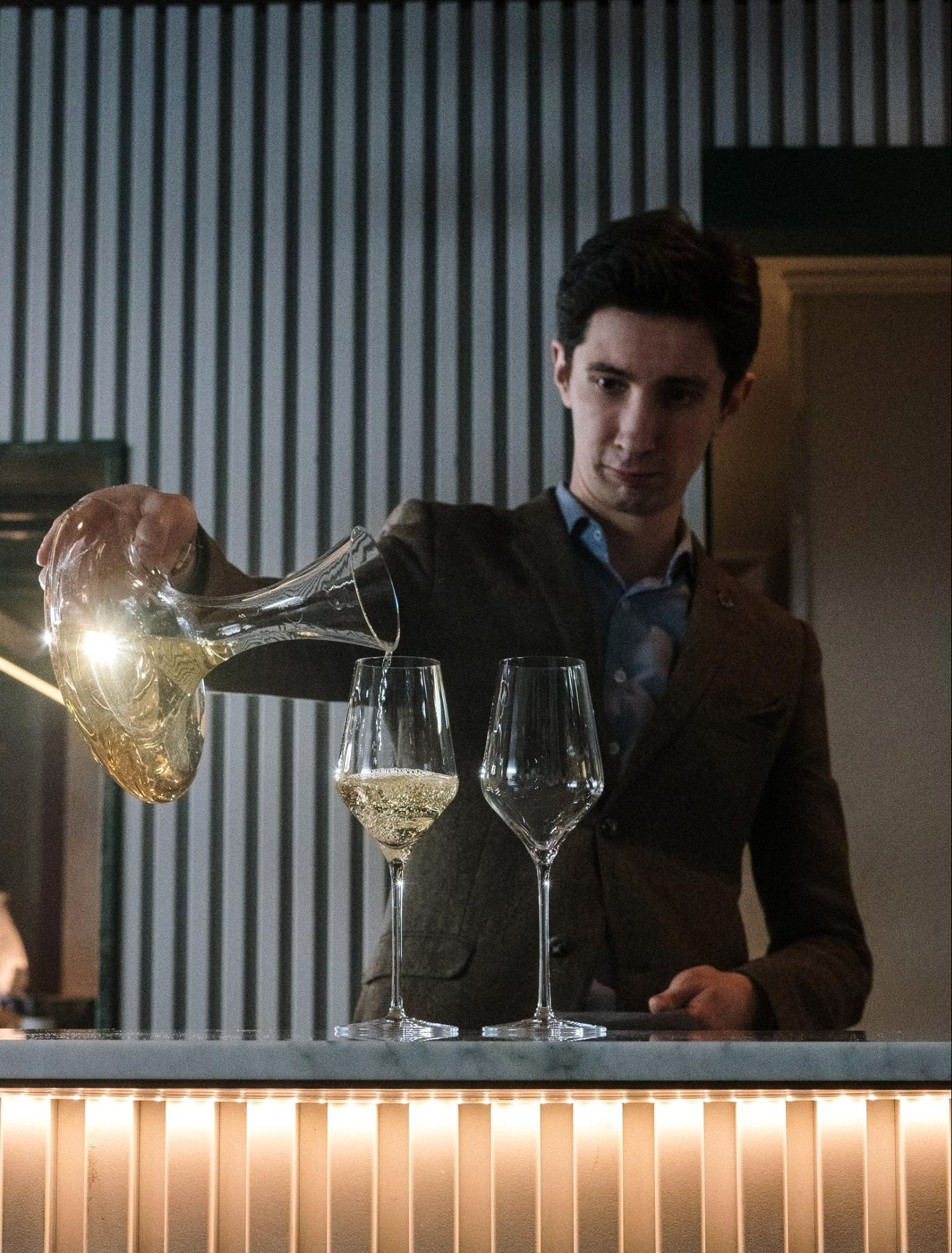 Man pouring white wine; Wine sommelier