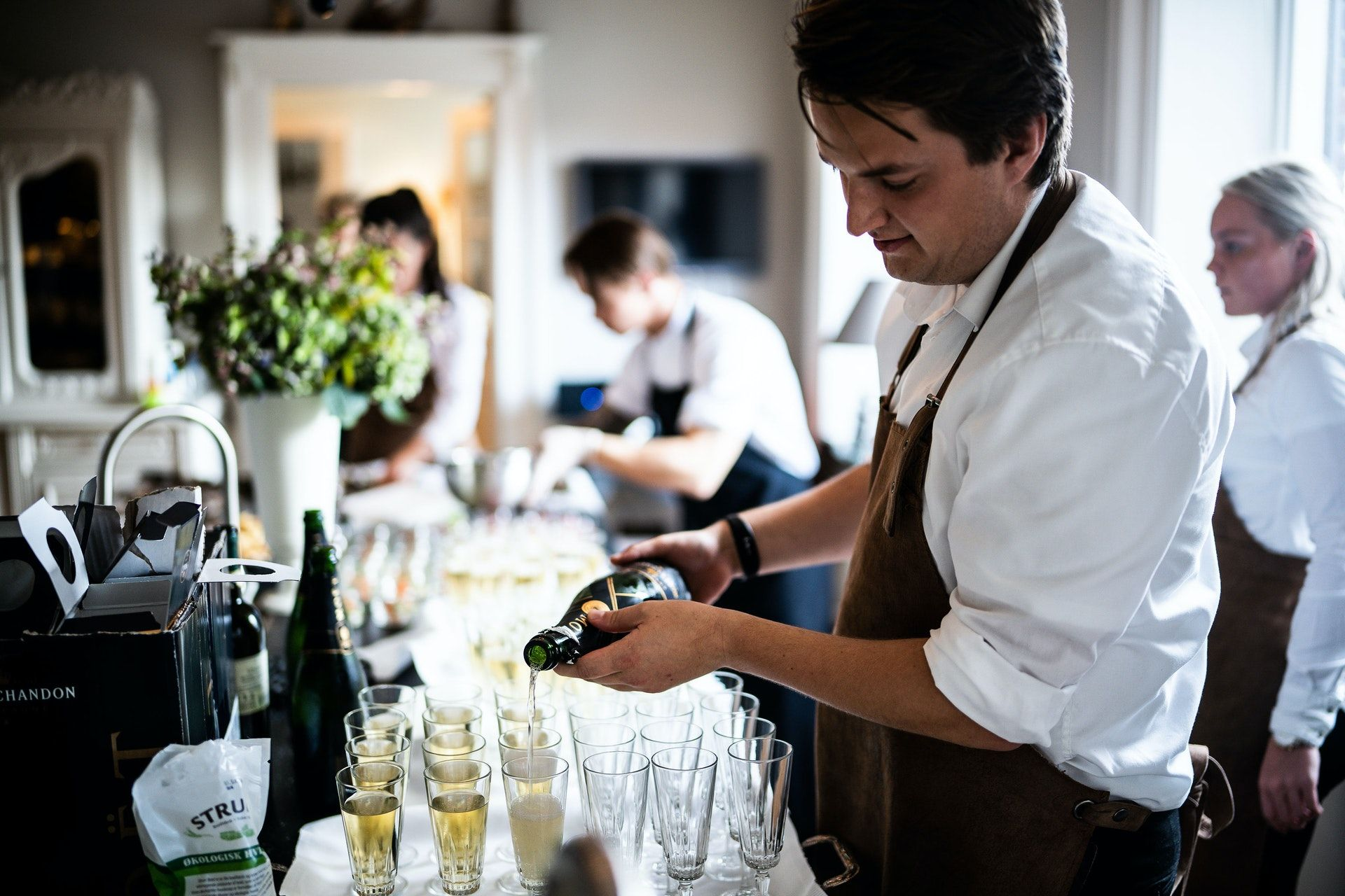 Waiter pouring champagne; WSET Level 1 exam