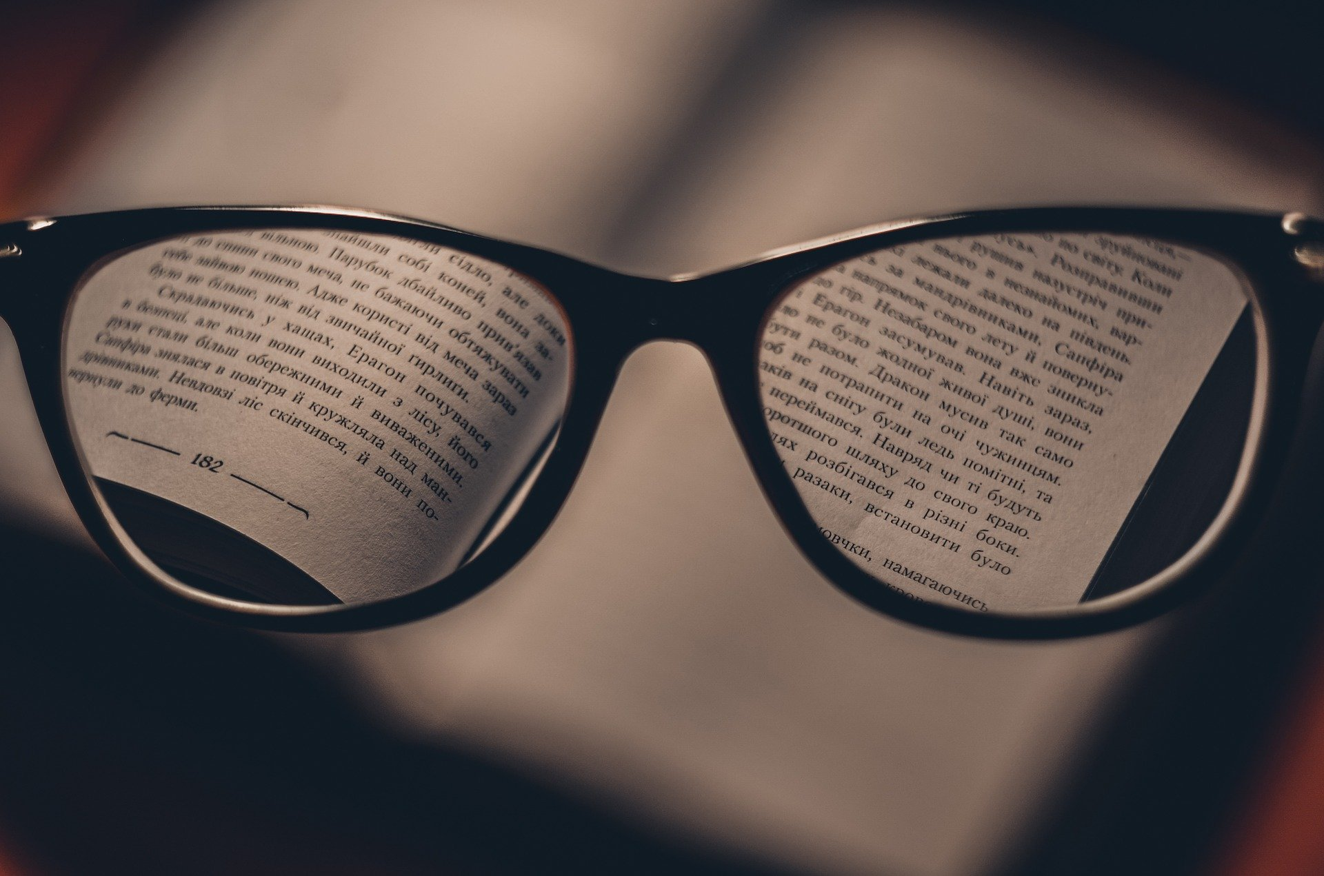 glasses showing the words clearly in a blurry book, bad vision fixed with glasses